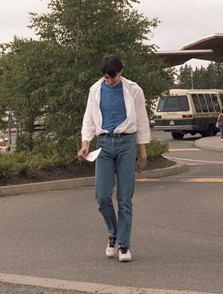 Old photo of Dave avoiding the camera while wearing too-tight jeans, a blue T-shirt, and a flowing white dress shirt tucked into his jeans which is opened to the navel.