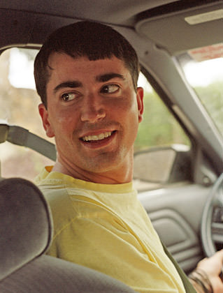 Dave as a totally hot young man looking back while driving a car.