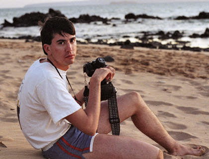 Dave sitting on a Hawaiian beach with his camera looking disappointed and wearing shorts that are too short.