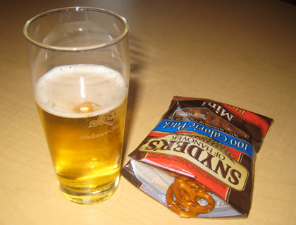 A glass of Budweiser and a bag of pretzels