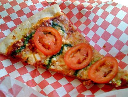 """A slice of David's """"Da Vinci"""" pizza with pesto and feta cheese."""