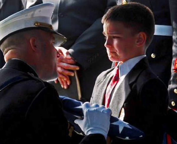 Young boy receives a flag from his father's funeral.